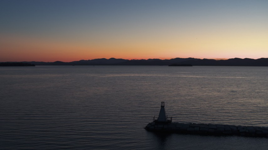 5.7K stock footage aerial video reverse view of Lake Champlain at twilight, reveal a lighthouse, Burlington, Vermont Aerial Stock Footage | DX0002_226_003