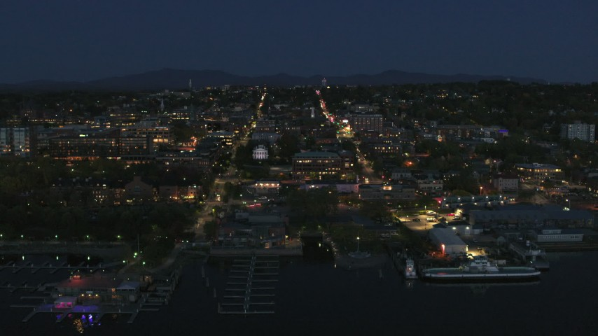 5.7K stock footage aerial video focus on the city's downtown area lit up for the night, fly away from marinas, Burlington, Vermont Aerial Stock Footage | DX0002_226_028