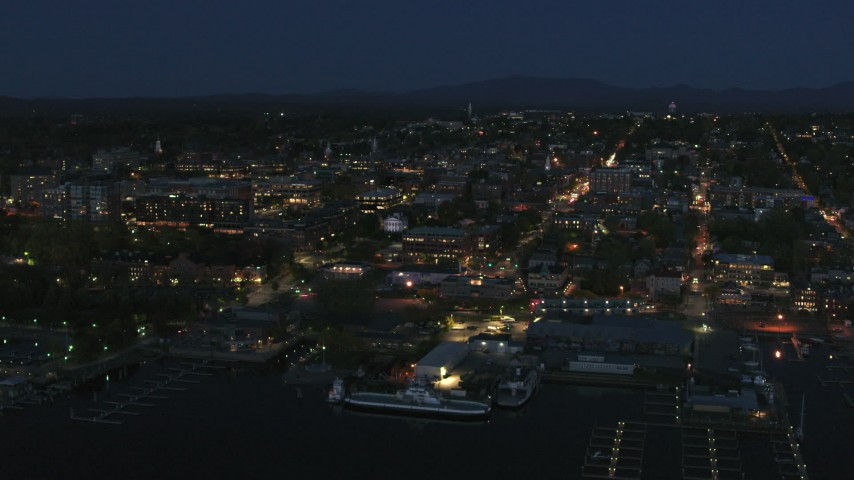 5.7K stock footage aerial video focus on the city's downtown area lit up for the night, seen from marinas, Burlington, Vermont Aerial Stock Footage | DX0002_226_029