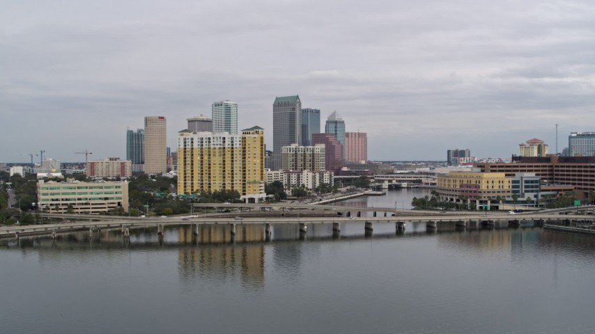 5.7K stock footage aerial video the city skyline behind a condo complex and channel, Downtown Tampa, Florida Aerial Stock Footage | DX0003_229_037
