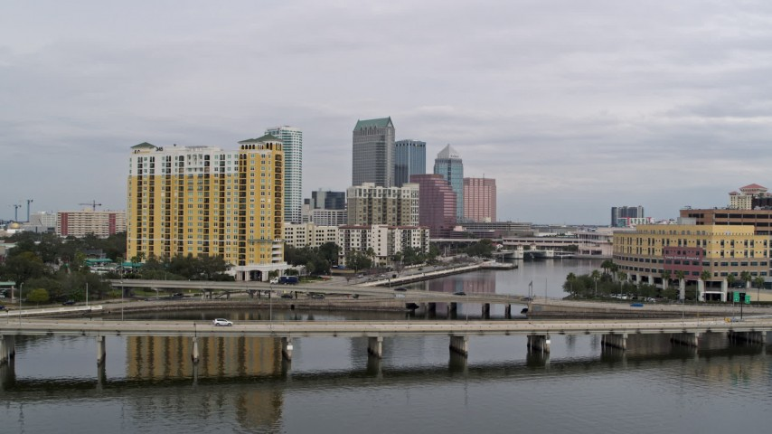 5.7K stock footage aerial video fly over a bridge and ascend toward the city skyline behind a condo complex, Downtown Tampa, Florida Aerial Stock Footage | DX0003_229_038