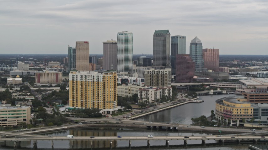 5.7K stock footage aerial video of the skyline seen while passing bridges and channel, Downtown Tampa, Florida Aerial Stock Footage | DX0003_230_007