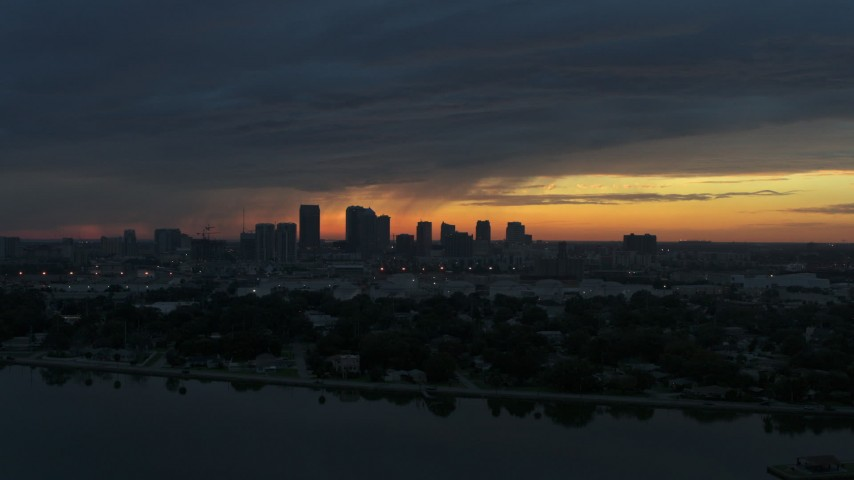 5.7K stock footage aerial video ascend over McKay Bay while focused on the Downtown Tampa skyline at sunset, Florida Aerial Stock Footage | DX0003_231_047
