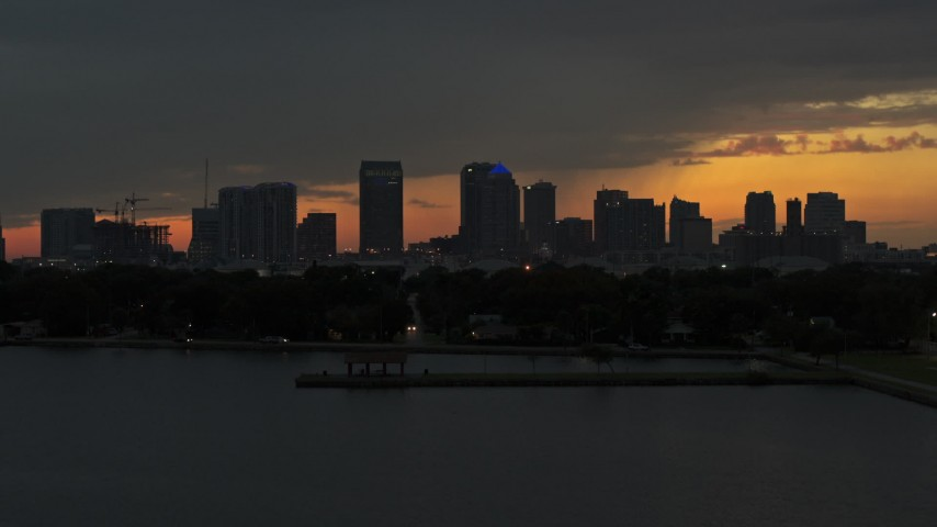 5.7K stock footage aerial video ascend from the bay toward the Downtown Tampa skyline at twilight, Florida Aerial Stock Footage | DX0003_232_011