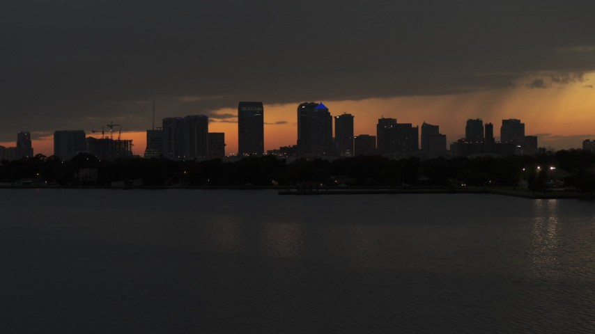 5.7K stock footage aerial video fly low over bay with view of skyscrapers in the Downtown Tampa skyline at twilight, Florida Aerial Stock Footage | DX0003_232_020