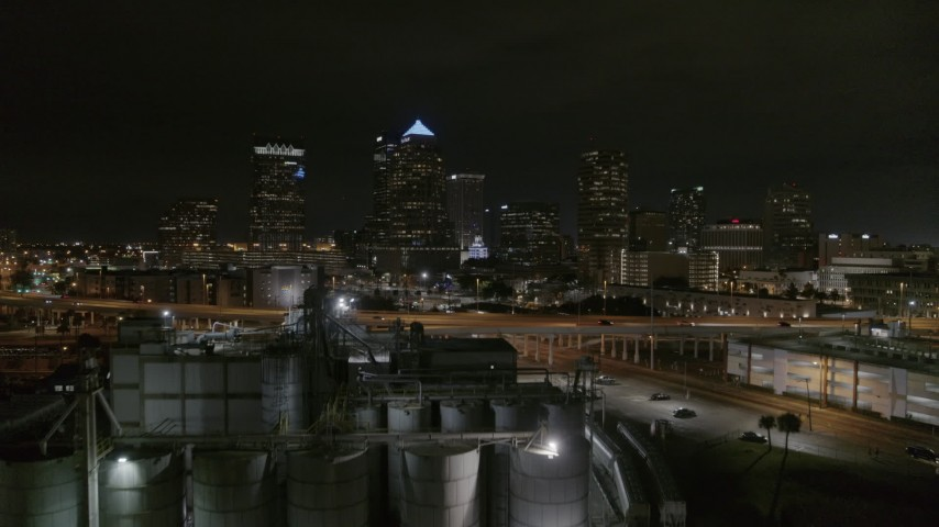 5.7K stock footage aerial video fly over flour mill to approach skyscrapers at night in Downtown Tampa, Florida Aerial Stock Footage | DX0003_232_029