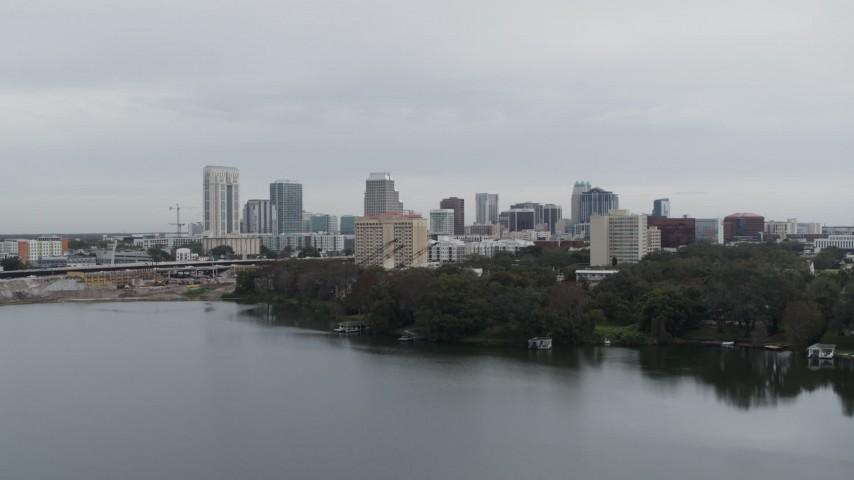 5.7K stock footage aerial video fly over lake toward the city's skyline, Downtown Orlando, Florida Aerial Stock Footage | DX0003_233_005