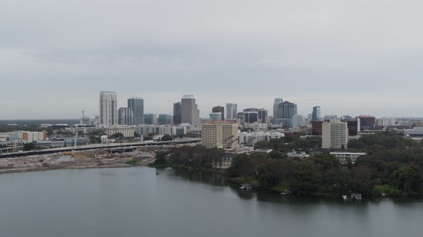 5.7K stock footage aerial video ascend from lake near hotel for view of the city's skyline, Downtown Orlando, Florida Aerial Stock Footage | DX0003_233_007