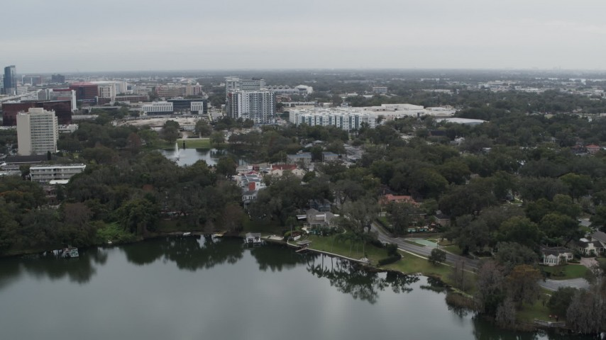 5.7K stock footage aerial video descend toward lakeside park while focused on apartment buildings in Orlando, Florida Aerial Stock Footage | DX0003_233_020