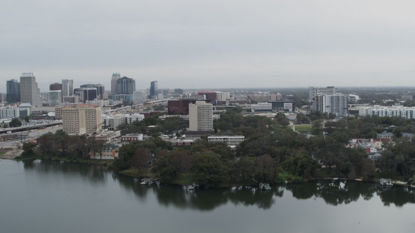 5.7K stock footage aerial video of office building by a lake, city's skyline in the background, Downtown Orlando, Florida Aerial Stock Footage | DX0003_233_023