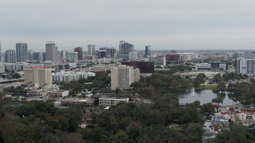 5.7K stock footage aerial video ascend from lake toward office building and city's skyline, Downtown Orlando, Florida Aerial Stock Footage | DX0003_233_024
