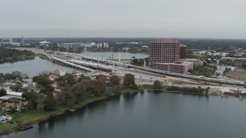 5.7K stock footage aerial video of flying by light freeway traffic and office building by a lake in Orlando, Florida Aerial Stock Footage | DX0003_233_027