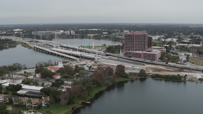 5.7K stock footage aerial video of flying away from light freeway traffic and office building by a lake in Orlando, Florida Aerial Stock Footage | DX0003_233_028