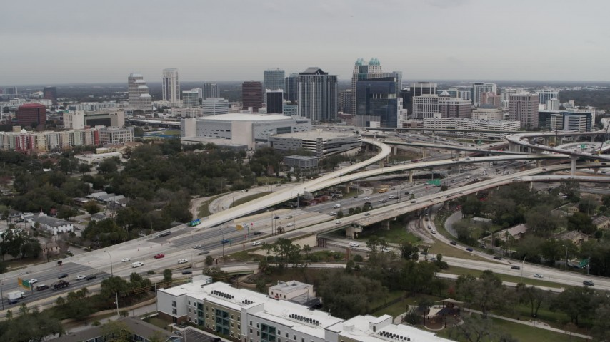 5.7K stock footage aerial video descend past Amway Center, city skyline beside freeway interchange, Downtown Orlando, Florida Aerial Stock Footage | DX0003_234_005