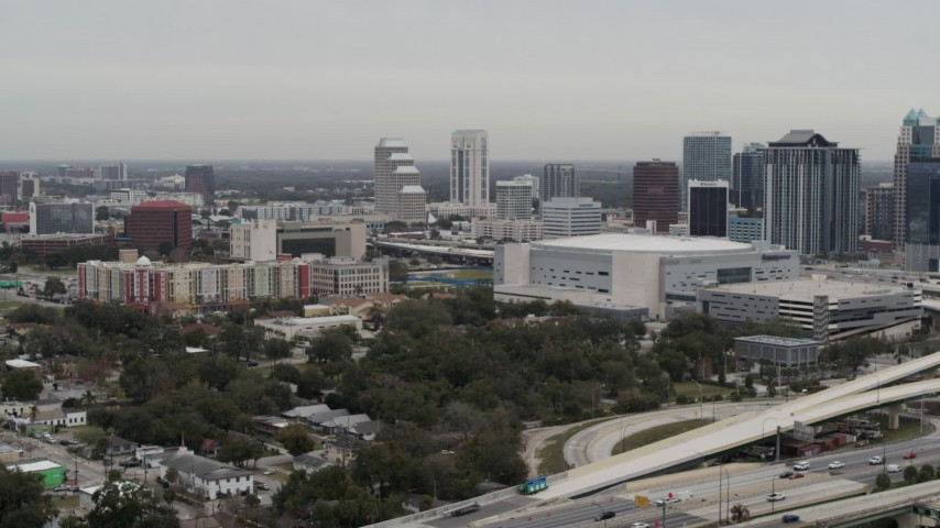 5.7K stock footage aerial video flying by apartment complex, Amway Center and city skyline, Downtown Orlando, Florida Aerial Stock Footage | DX0003_234_024