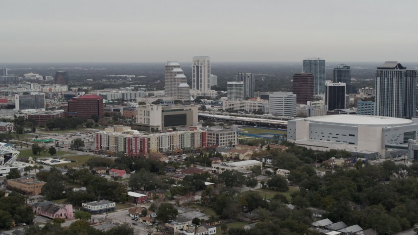 5.7K stock footage aerial video flying past apartment complex near Amway Center and city skyline, Downtown Orlando, Florida Aerial Stock Footage | DX0003_234_026