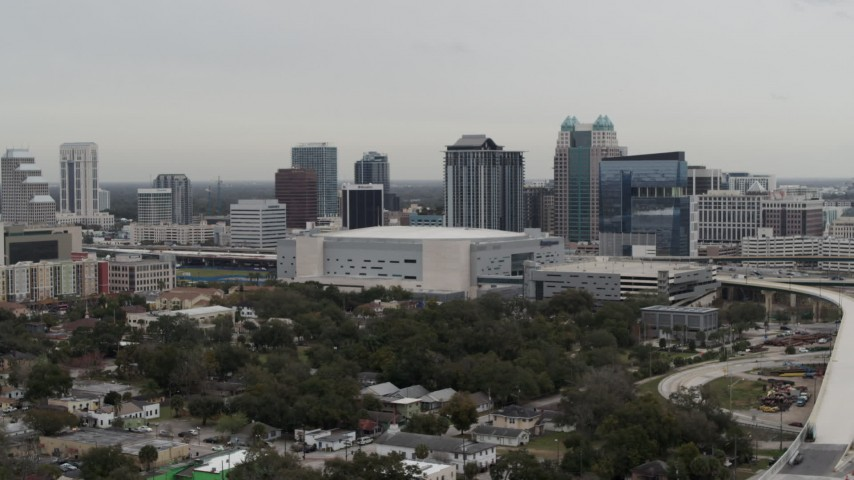 5.7K stock footage aerial video descend past Amway Center arena and city skyline, Downtown Orlando, Florida Aerial Stock Footage   DX0003_234_030