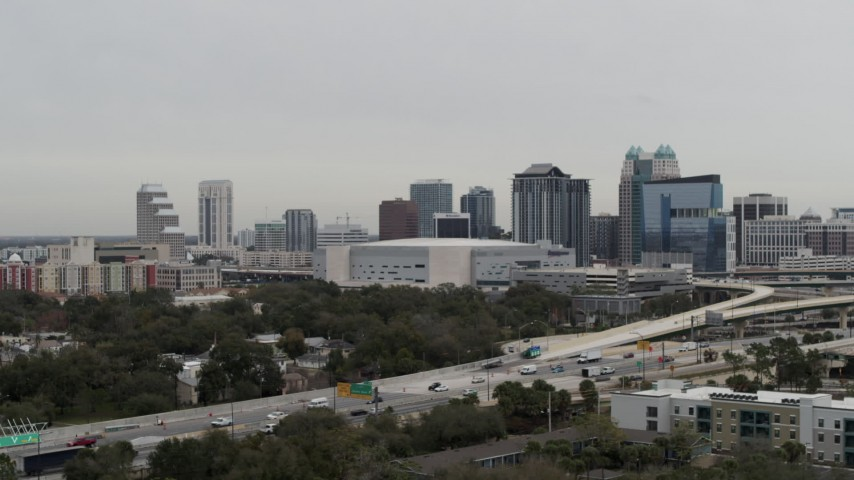 5.7K stock footage aerial video fly away from Amway Center arena and city skyline, Downtown Orlando, Florida Aerial Stock Footage | DX0003_234_031