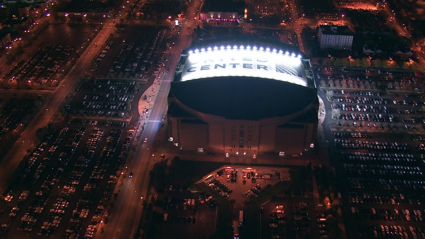 HD stock footage aerial video approach and tilt to United Center at night, Downtown Chicago skyline in the background, Illinois Aerial Stock Footage | ED0001_000007