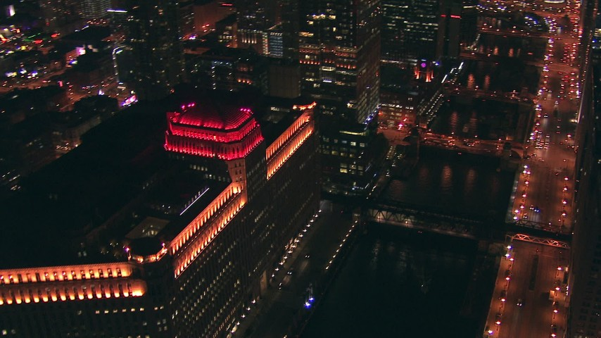 HD stock footage aerial video pan from the Merchandise Mart to the Chicago River bridges and skyscrapers at night, Downtown Chicago, Illinois Aerial Stock Footage | ED0001_000073