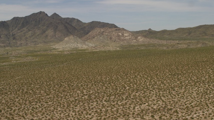 4K stock footage aerial video pan across Dead Mountains Wilderness Area, seen from flat Mojave Desert plain in Laughlin, Nevada Aerial Stock Footage | FG0001_000025
