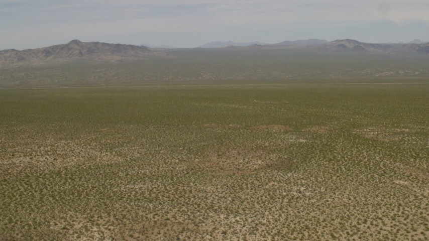 4K stock footage aerial video tilt to reveal distant mountains and fly over open Mojave Desert in Laughlin, Nevada Aerial Stock Footage | FG0001_000032