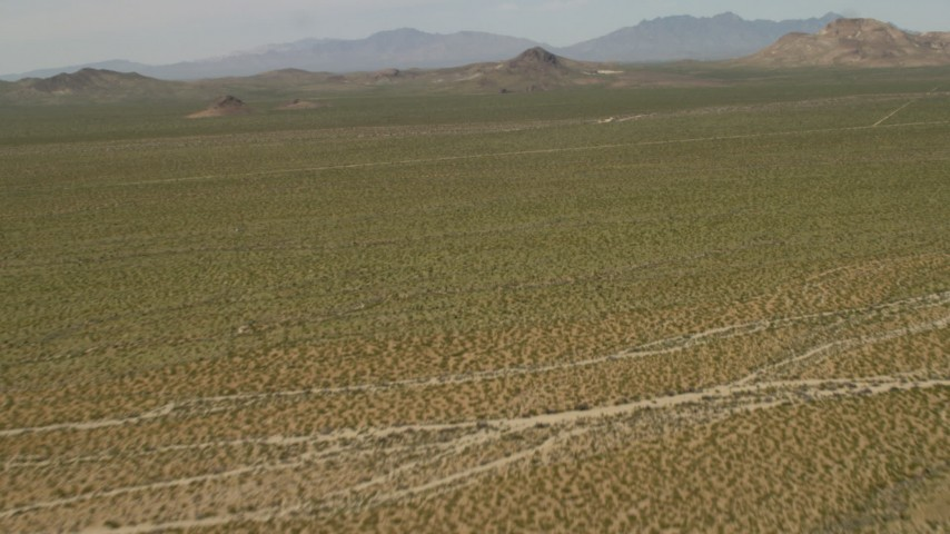 Fly over Mojave Desert landscape to approach hills in San Bernardino County, California Aerial Stock Footage | FG0001_000040
