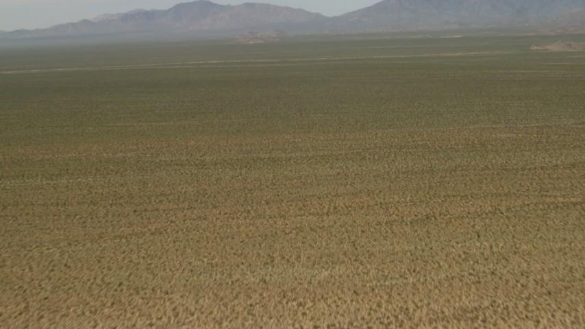 4K stock footage aerial video fly over arid desert to approach mountains in Mojave Desert, San Bernardino County, California Aerial Stock Footage | FG0001_000043