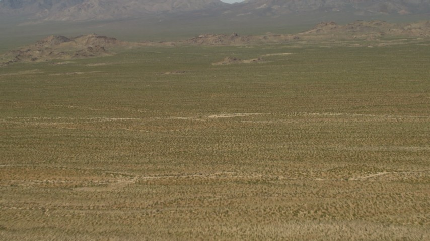 4K stock footage aerial video fly over the Mojave Desert to approach hills and mountains in San Bernardino County, California Aerial Stock Footage | FG0001_000045