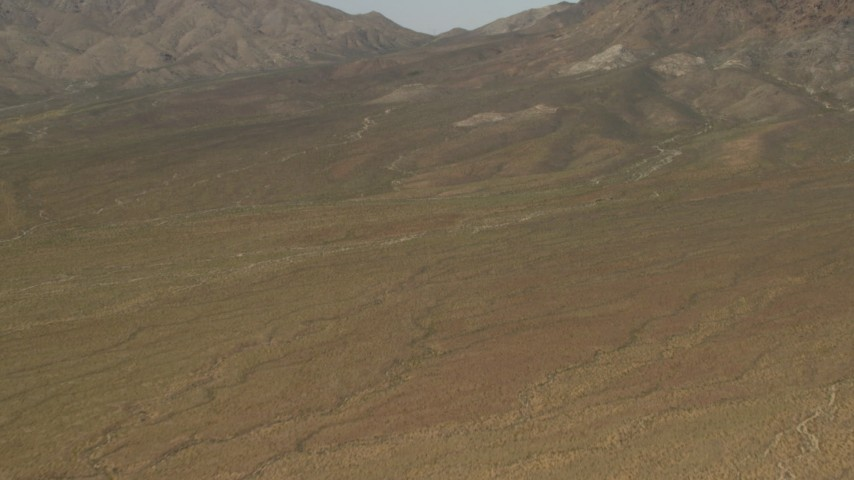 Tilt to approach mountains in the Mojave Desert in San Bernardino County, California Aerial Stock Footage | FG0001_000047