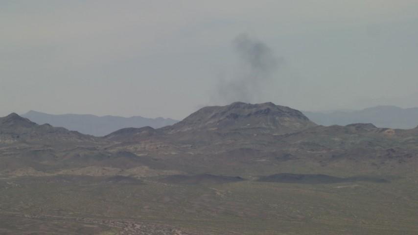 Smoke rising from behind a Mojave Desert mountain in San Bernardino County, California Aerial Stock Footage | FG0001_000054