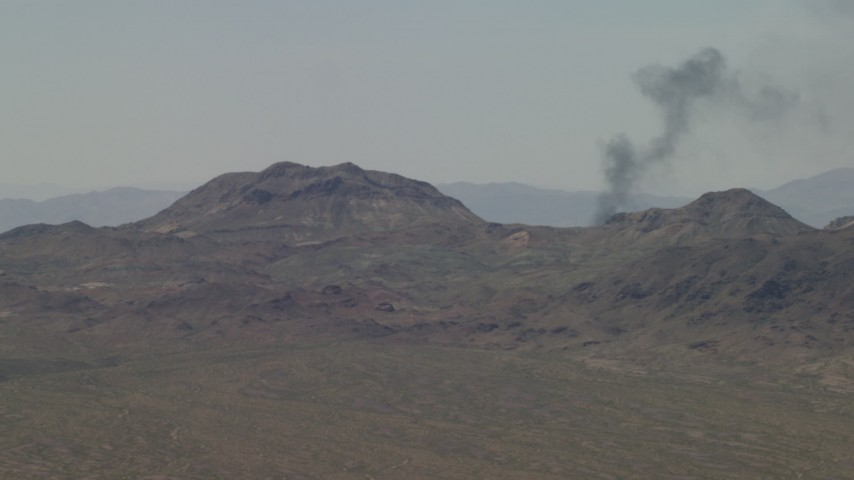 4K stock footage aerial video of a smoke column behind Mojave Desert mountains in San Bernardino County, California Aerial Stock Footage | FG0001_000055