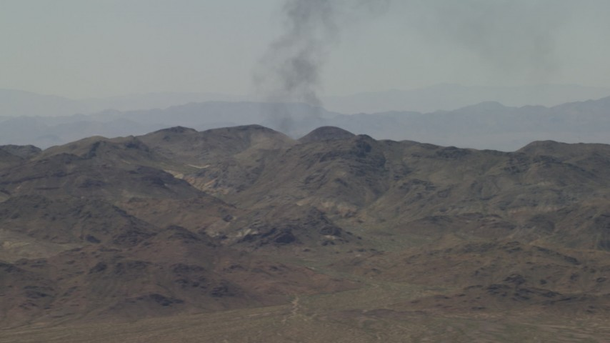 4K stock footage aerial video of a column of black smoke rising behind Mojave Desert mountains in San Bernardino County, California Aerial Stock Footage   FG0001_000056