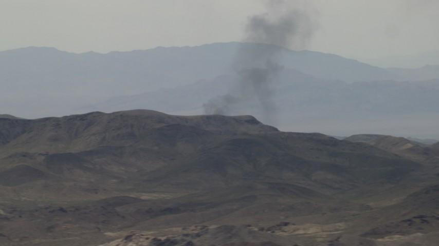 4K stock footage aerial video of black smoke rising behind Mojave Desert mountains in San Bernardino County, California Aerial Stock Footage   FG0001_000057