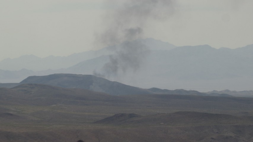 Zoom on black smoke rising behind Mojave Desert mountains in San Bernardino County, California Aerial Stock Footage   FG0001_000058