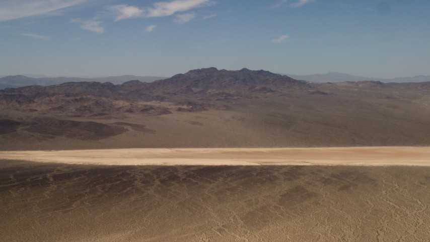 4K stock footage aerial video approach a dry lake near Mojave Desert mountains in San Bernardino County, California Aerial Stock Footage | FG0001_000060