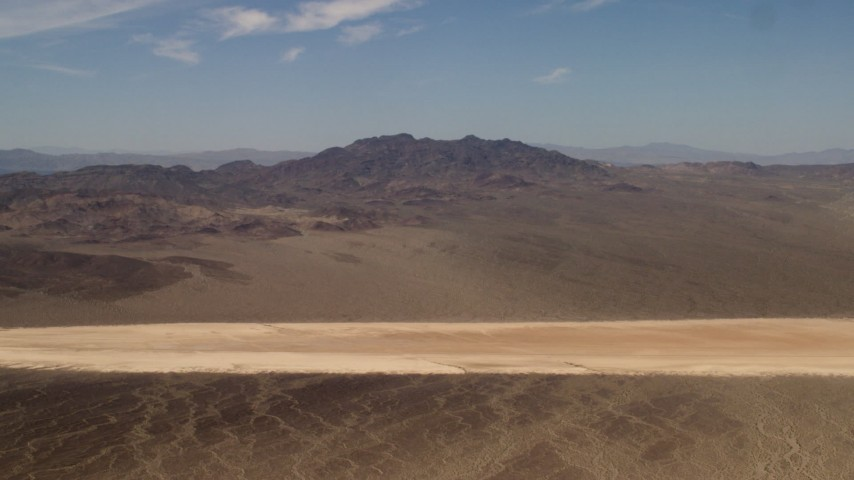 Slow approach to a dry lake near Mojave Desert mountains in San Bernardino County, California Aerial Stock Footage | FG0001_000061
