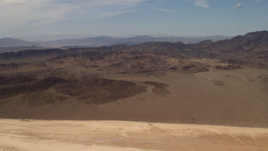 4K stock footage aerial video pan across Mojave Desert mountains, seen from a dry lake in San Bernardino County, California Aerial Stock Footage | FG0001_000064