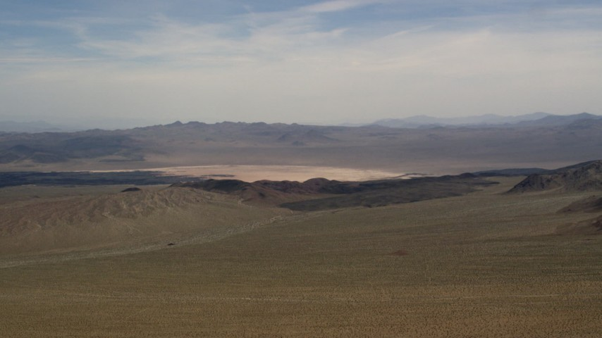 A dry lake and distant mountains in the Mojave Desert, San Bernardino County, California Aerial Stock Footage FG0001_000095