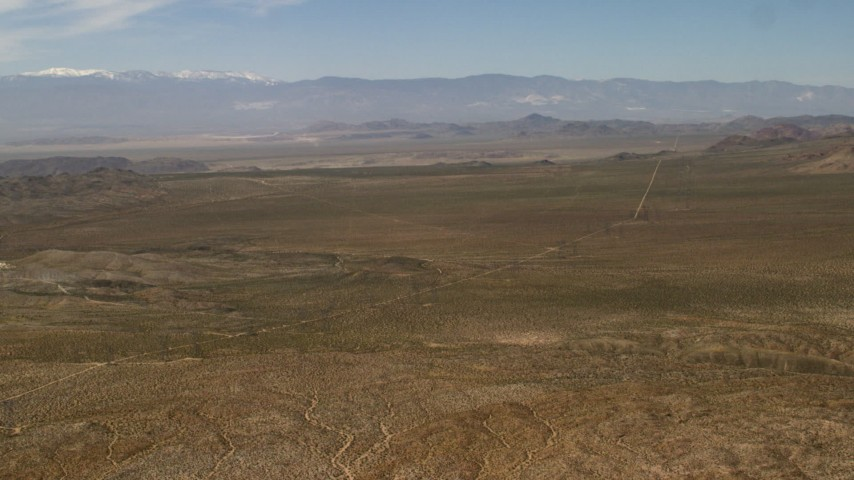 4K stock footage aerial video pan across desert plain and road to reveal Iron Ridge in the Mojave Desert, San Bernardino County, California Aerial Stock Footage | FG0001_000104