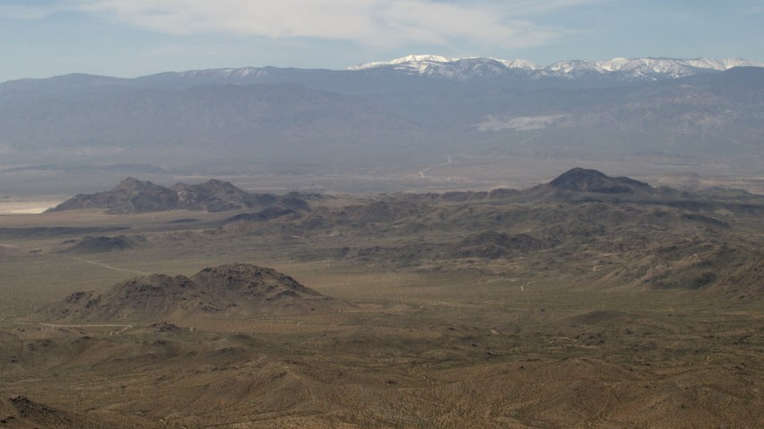 A view of the San Bernardino Mountains with snow from Mojave Desert mountains, San Bernardino County, California Aerial Stock Footage | FG0001_000115