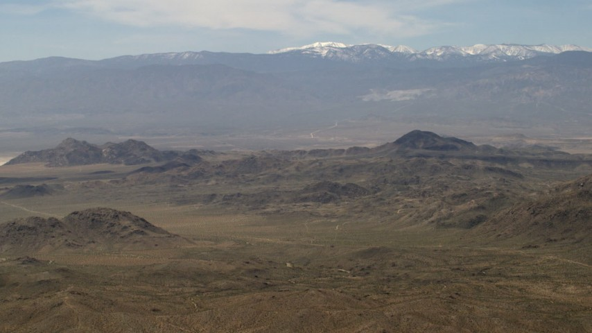 A view of snowy San Bernardino Mountains from Mojave Desert mountains, San Bernardino County, California Aerial Stock Footage | FG0001_000116