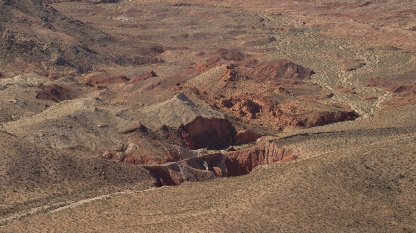 4K stock footage aerial video of sheer red slopes of rocky hills around a shallow box canyon in the Nevada Desert Aerial Stock Footage | FG0001_000253