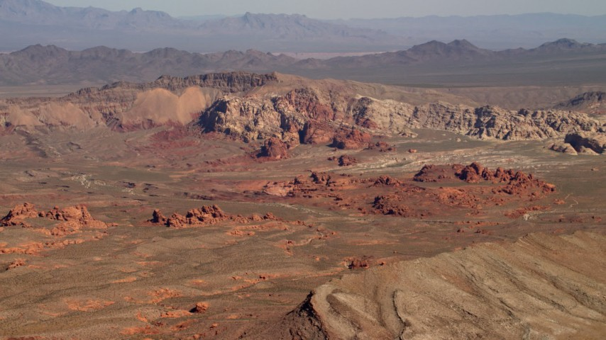 Red rock formations near a mountain ridge in the Nevada Desert Aerial Stock Footage | FG0001_000258