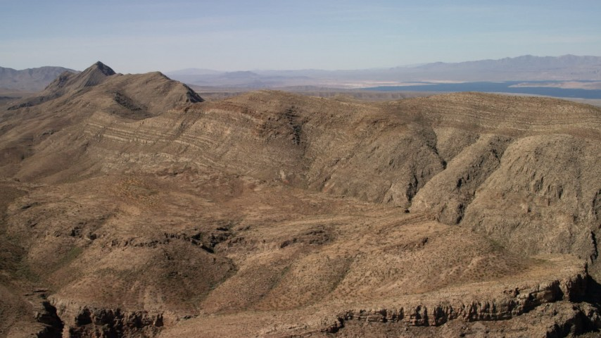 4K stock footage aerial video of steep-sloped mountain ridges in the Nevada Desert and Lake Mead in the background Aerial Stock Footage | FG0001_000261