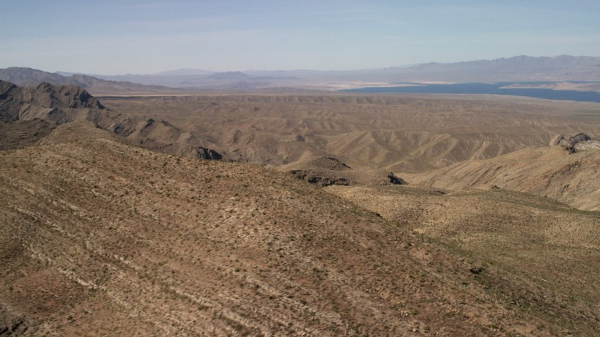 Flyby steep-sloped mountain ridges in the Nevada Desert near rolling hills and Lake Mead Aerial Stock Footage | FG0001_000262