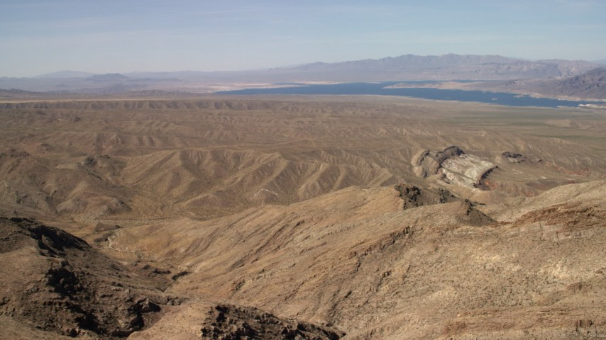 Pan across desert hills and approach a scarred hill, with Lake Mead in the background, Nevada Desert Aerial Stock Footage | FG0001_000263