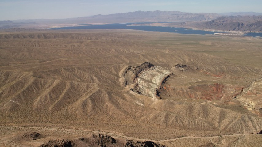 4K stock footage aerial video approach a scarred hillside with Lake Mead in the background, Nevada Desert Aerial Stock Footage | FG0001_000264