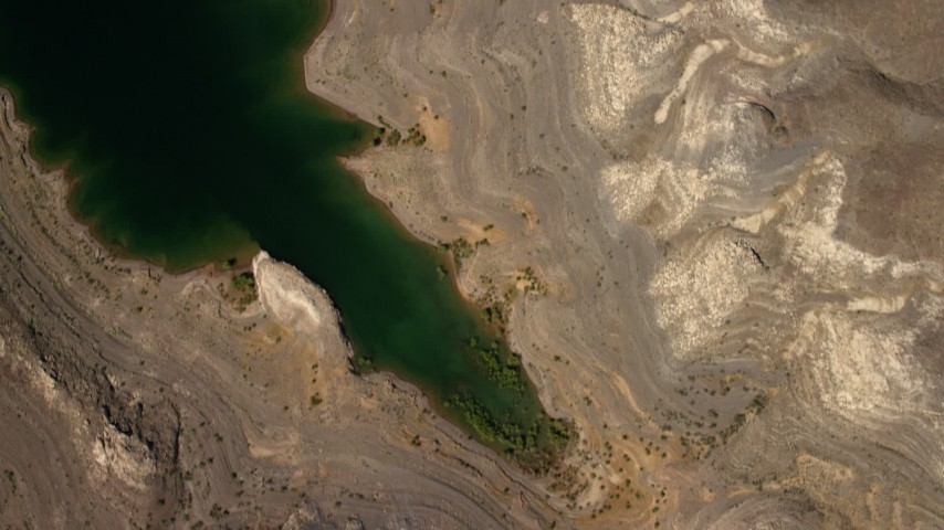 An overhead view of flat plain the Nevada Desert, and reveal the shore of Lake Mead Aerial Stock Footage | FG0001_000273