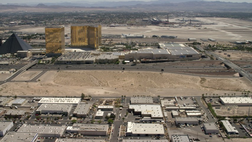 Tilt from an open dirt lot beside I-15 with light traffic in Las Vegas, Nevada to casino resorts on the Strip Aerial Stock Footage | FG0001_000351